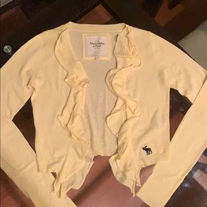 light yellow open cardigan with ruffles on the end